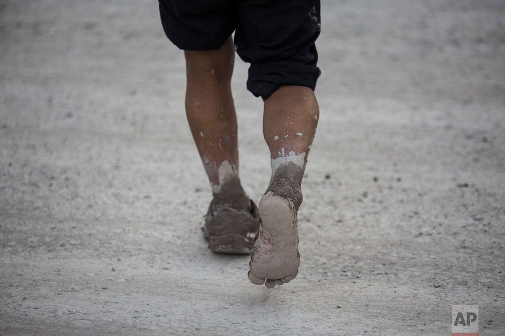 In this Jan. 13, 2017 photo, a man walks to a shelter in the mud stricken t town of Volcan, Jujuy province, Argentina. The mudslide was caused by the Intense rains that hit the area one week ago, flooding the town with mud, killing several and causing the evacuation of thousands. (Gianni Bulacio/Infoto via AP)