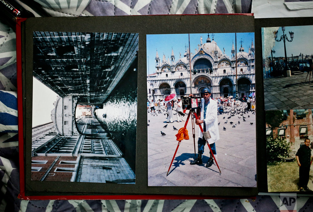 In this Dec. 20, 2016 photo, Luis Maldonado's photo album holds images of his trip to Venice, at his home in Santiago, Chile. He remains proud of the work he did at the 2003 Venice Biennale in an exhibit about traditional Chilean art forms by artist Eugenia Vargas, using his box camera to photograph people who lined up to have their portraits taken. (AP Photo/Esteban Felix)