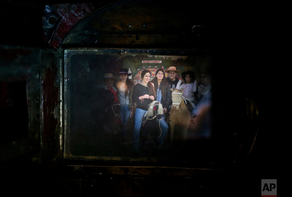 In this Sept. 4, 2016 photo, a family having their portrait taken fills the viewfinder of Luis Maldonado's old wooden old box camera, during a fair marking Independence Day in Santiago, Chile. The box camera's mechanism is simple: light enters through a lens and the photographic paper inside it captures a negative image of the subject photographed. (AP Photo/Esteban Felix)