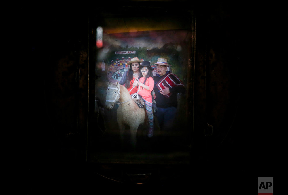 In this Sept. 4, 2016 photo, a family having their portrait taken fills the viewfinder of Luis Maldonado's old wooden old box camera, during a fair marking Independence Day in Santiago, Chile. At about $7.50 per portrait, a box camera photograph costs more than twice as much as the $3 charged for a digital one. (AP Photo/Esteban Felix)