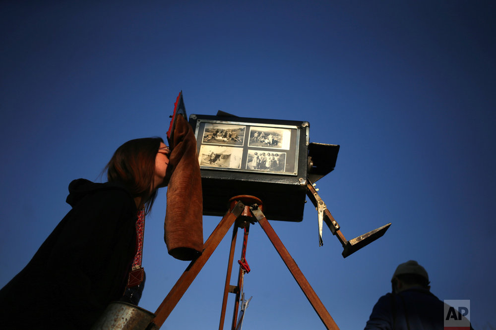 In this Sept. 4, 2016 photo, a woman looks through the viewfinder of the old wooden box camera used by photographer Luis Maldonado during a fair marking Independence Day in Santiago, Chile. Chile's box photographers union had more than 5,000 members by 1942, but that number plunged to about 300 by 1972, according to Chilean historian Octavio Cornejo. (AP Photo/Esteban Felix)