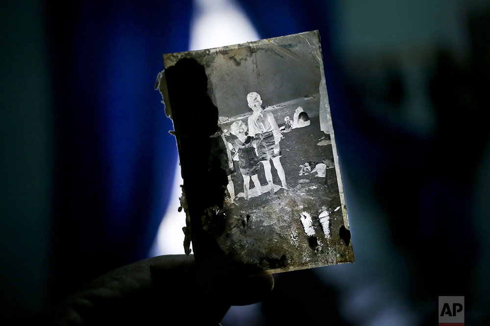 In this Dec. 20, 2016 photo, street photographer Luis Maldonado shows a negative that he says was made by his grandfather, his father, or his uncle, at his home in Santiago, Chile. Once the negative has been developed, the photographer takes a picture of the negative image, using his arm to hold a special paper in front of the lens to get a positive print. (AP Photo/Esteban Felix)