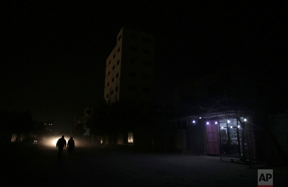 In this Monday, Jan. 16, 2017 photo, Palestinians walk on a dark street next to a grocery shop lit with a lamps powered by a battery during a power cut in Gaza City. (AP Photo/ Khalil Hamra)
