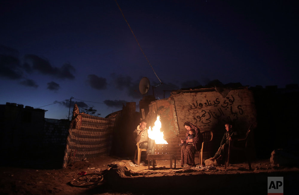 In this Sunday, Jan. 15, 2017 photo, a Palestinian family warm themselves up with a fire outside their makeshift house during a power cut in a poor neighborhood in town of Khan Younis in the southern Gaza Strip. (AP Photo/ Khalil Hamra)