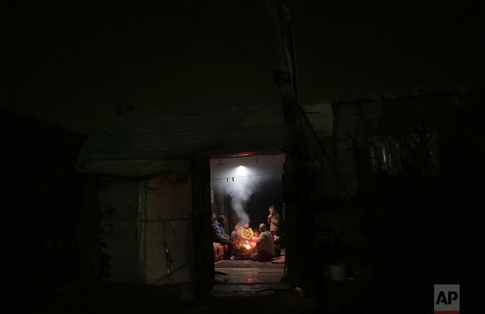 In this Sunday, Jan. 15, 2017 photo, a Palestinian family warm themselves up with a fire inside their makeshift house during the power cut in a poor neighborhood in town of Khan Younis in the southern Gaza Strip. (AP Photo/ Khalil Hamra)