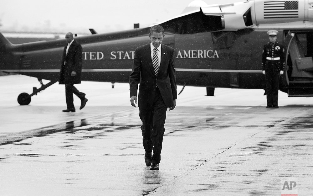 President Barack Obama walks across the tarmac in a light drizzle in Chicago, Wednesday, April 27, 2011, to travel to New York City for campaign fundraising events. (AP Photo/Charles Dharapak)
