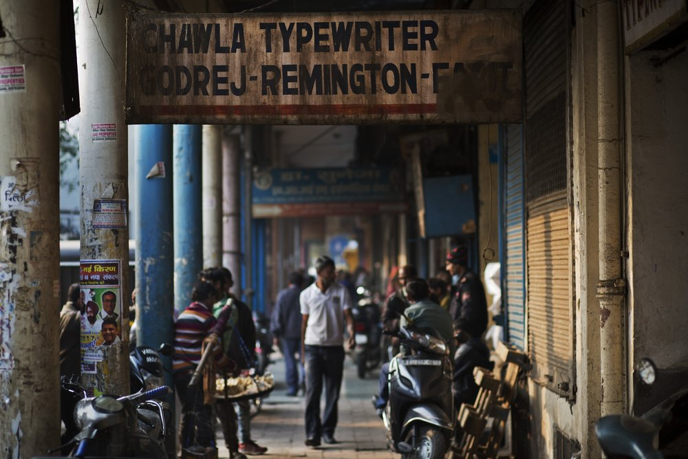 In this Jan. 16, 2017 photo, a rusted billboard of a typewriter shop hangs in an alley of New Delhi, India. The country still has a few thousand remaining professional typists. There are a handful of typewriter repairmen and stores selling spare parts. There are typing schools that, at least occasionally, are jammed with students. But even in this country, one of the last places in the world where the typewriter remains a part of everyday life, the end is, finally, coming. (AP Photo/Bernat Armangue)