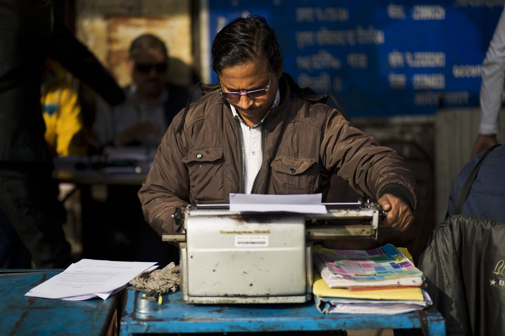 In this Jan. 18, 2017 photo, a roadside professional typist works near Delhi's stock exchange market in New Delhi, India. India still has a few thousand remaining professional typists. There are a handful of typewriter repairmen and stores selling spare parts. There are typing schools that, at least occasionally, are jammed with students. But even in this country, one of the last places in the world where the typewriter remains a part of everyday life, the end is, finally, coming. (AP Photo/Bernat Armangue)