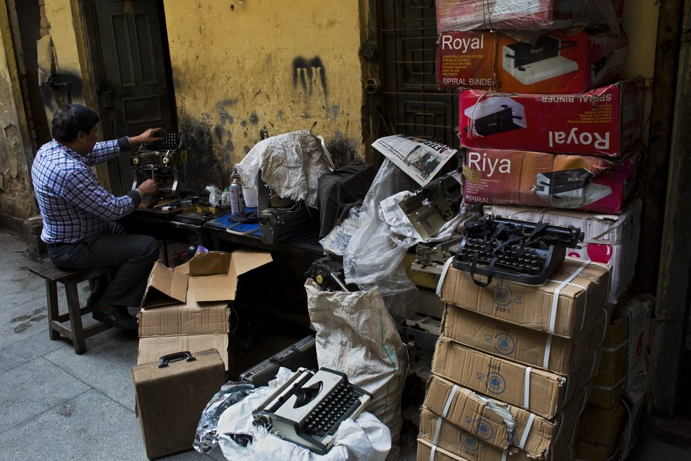 In this Jan. 18, 2017 photo, professional typists work on a roadside near Delhi's stock exchange market in New Delhi, India. India is one of the last places in the world where the typewriter continues to cling to life. This country has thousands of professional typists, most of them working outside the country's courts and government offices. But even in India, where stodgy government bureaucracies have helped the typewriter survive, its twilight is at hand. (AP Photo/Bernat Armangue)