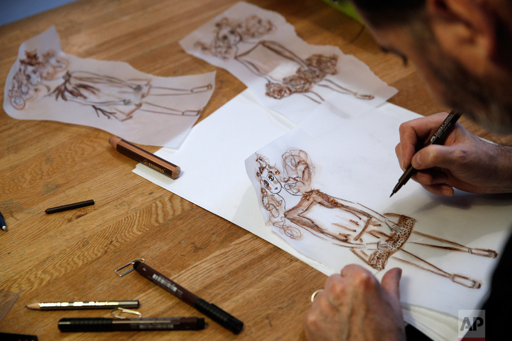 French fashion designer Franck Sorbier draws his Spring-Summer 2017 Haute Couture fashion collection, in Paris, Thursday, Oct. 27, 2016. From the earliest ink sketches to the final touches on this season's stunning floral gowns, Frank Sorbier is one of the last Parisian couturiers to do it all himself. (AP Photo/Christophe Ena)