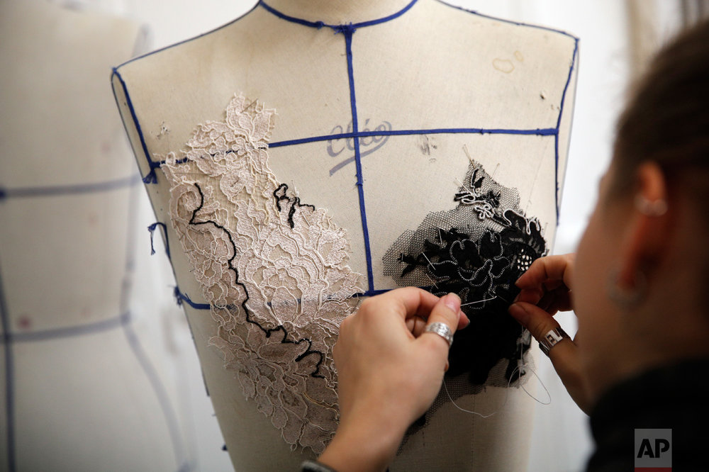 A seamstress sews at Franck Sorbier fashion house for his Spring-Summer 2017 Haute Couture collection, in Paris, Thursday, Oct. 27, 2016. From the earliest ink sketches to the final touches on this season's stunning floral gowns, Frank Sorbier is one of the last Parisian couturiers to do it all himself. (AP Photo/Christophe Ena)