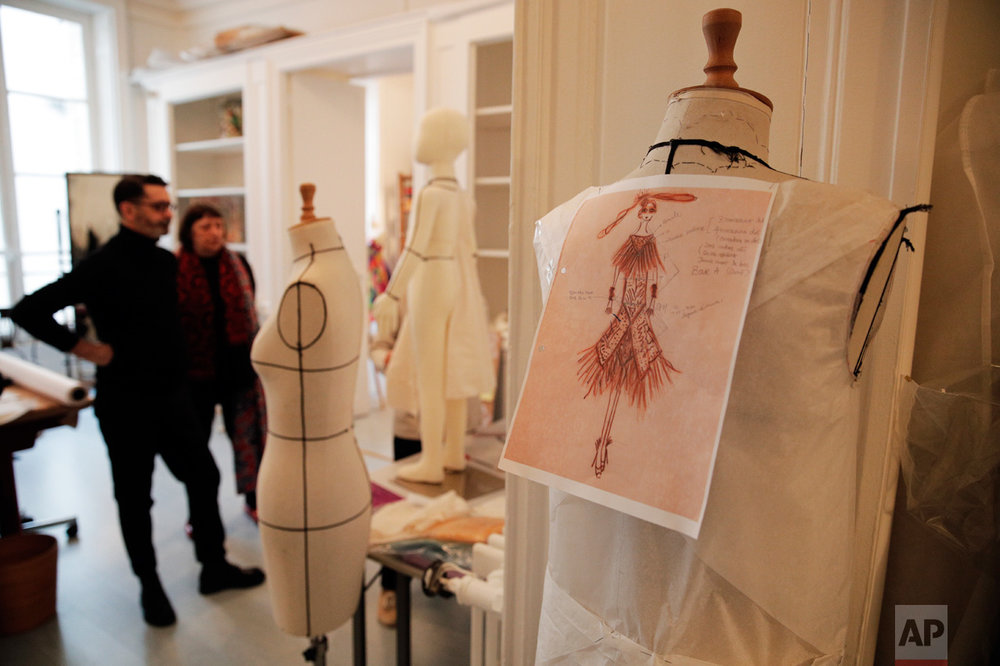 Isabelle Tartiere Sorbier, center left, and fashion designer Franck Sorbier watch a mannequin as they prepare the Spring-Summer 2017 Haute Couture collection, in Paris, Tuesday, Dec. 13, 2016. For the diaphanous spring-summer haute couture collection he showed in Paris this week, Sorbier burned the midnight oil with his small atelier team starting in October, as Associated Press photographers followed his creative process from conception to catwalk. (AP Photo/Christophe Ena)
