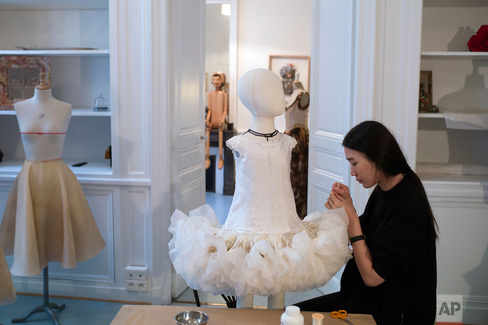 Seamstress Bihui works on a dress during the manufacturing of French designer Franck Sorbier' Spring-Summer 2017 Haute Couture fashion collection, in Paris, Friday, Dec. 23, 2016. From the earliest ink sketches to the final touches on this season's stunning floral gowns, Frank Sorbier is one of the last Parisian couturiers to do it all himself. (AP Photo/Thibault Camus)