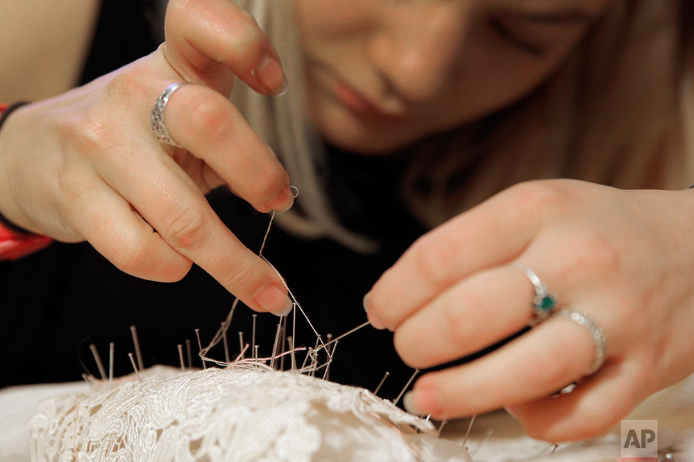 A seamstress sews at Franck Sorbier fashion house for his Spring-Summer 2017 Haute Couture collection, in Paris, Friday, Jan. 6, 2017. (AP Photo/Christophe Ena)
