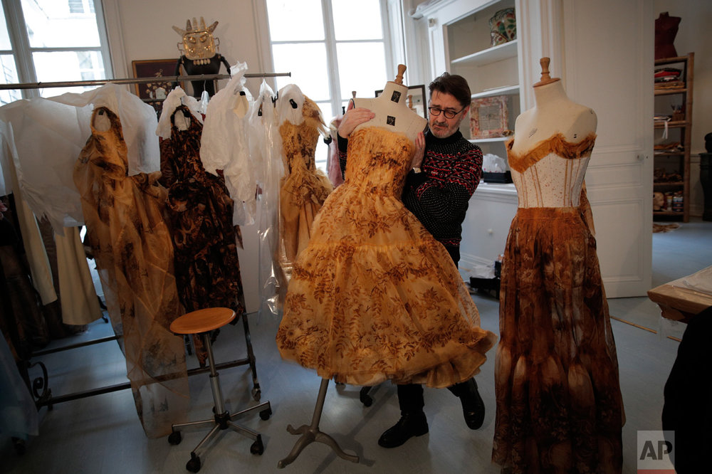 French fashion designer Franck Sorbier holds a mannequin with a dress for his Spring-Summer 2017 Haute Couture fashion collection, in Paris, Monday, Jan. 23, 2017. From the earliest ink sketches to the final touches on this season's stunning floral gowns, Frank Sorbier is one of the last Parisian couturiers to do it all himself. (AP Photo/Christophe Ena)
