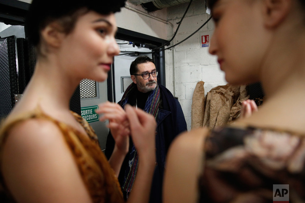 French fashion designer Franck Sorbier, center, supervises the backstage before his Spring-Summer 2017 Haute Couture fashion collection presented in Paris, Wednesday, Jan. 25, 2017. From the earliest ink sketches to the final touches on this season's stunning floral gowns, Frank Sorbier is one of the last Parisian couturiers to do it all himself. (AP Photo/Christophe Ena)