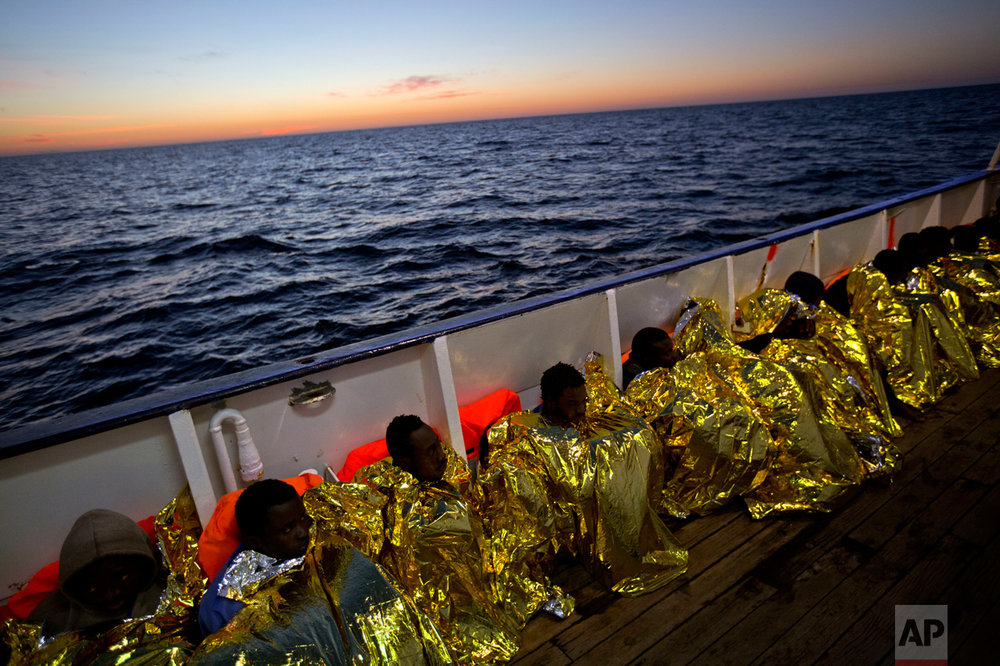 Wrapped in blankets, Sub-Saharan migrants sit on the deck of the ship Golfo Azzurro after their rescue from a rubber boat by members of the Proactive Open Arms organization in the Mediterranean sea, about 24 miles north of Sabratha, Libya, on Friday, Jan. 27, 2017. Tens of thousands of people seeking better lives are expected to trek across deserts and aboard unseaworthy boats from war-torn Libya this year in a desperate effort to reach European shores by way of Italy. (AP Photo/Emilio Morenatti)