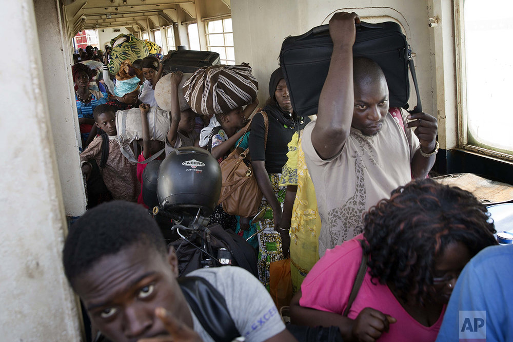 People wait to disembark from a ferry arriving at the port in Banjul, Gambia, Saturday Jan. 21, 2017, as life slowly returns to the Gambian capital. Gambia's defeated leader Yahya Jammeh announced early Saturday he has decided to relinquish power, after hours of last-ditch talks with regional leaders and the threat by a regional military force to make him leave. (AP Photo/Jerome Delay)
