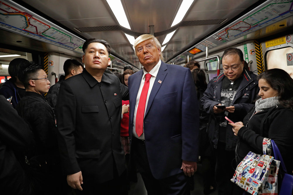 Kim Jong Un and Donald Trump impersonators, Howard, left, and Dennis, right, stand side by side on a train to promote a music video they created in Hong Kong, Wednesday, Jan. 25, 2017. (AP Photo/Vincent Yu)