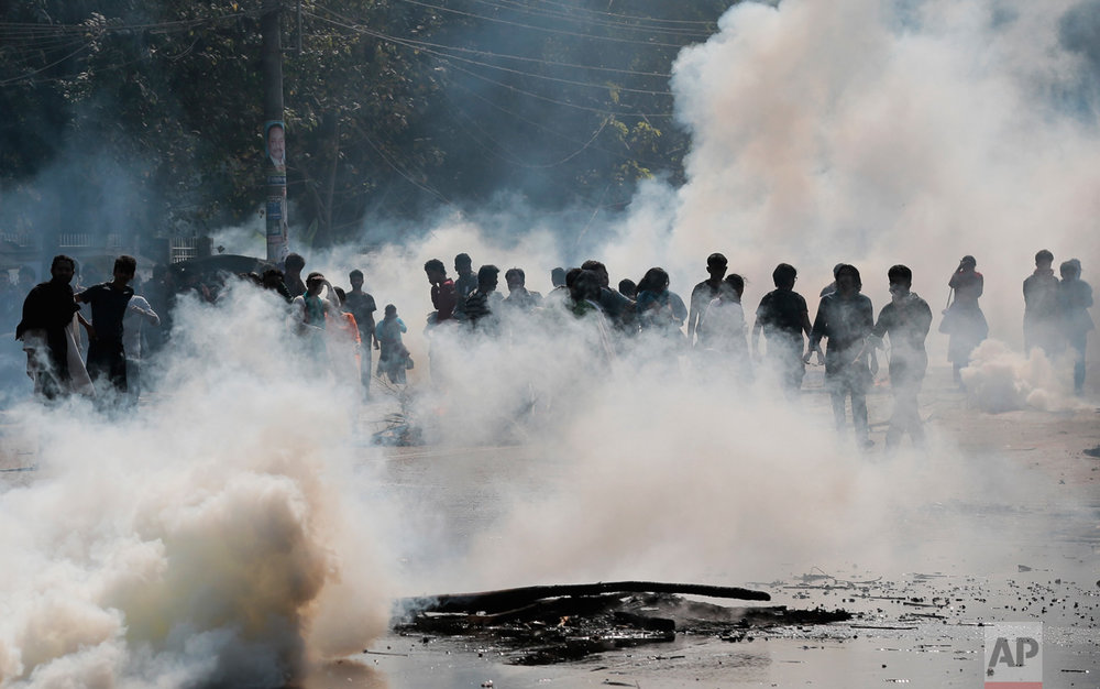 Police launch tear gas shells to disperse protestors demanding the cancellation of a plan for a massive coal-fired power plant near ecologically sensitive mangrove forests on the coast in Dhaka, Bangladesh, on Thursday, Jan. 26, 2017. The government insists that the planned 1.3-gigawatt Rampal power station near the Sundarbans, a world heritage site, is key to reaching its target of 24 gigawatts of electrical capacity by 2021. (AP Photo)