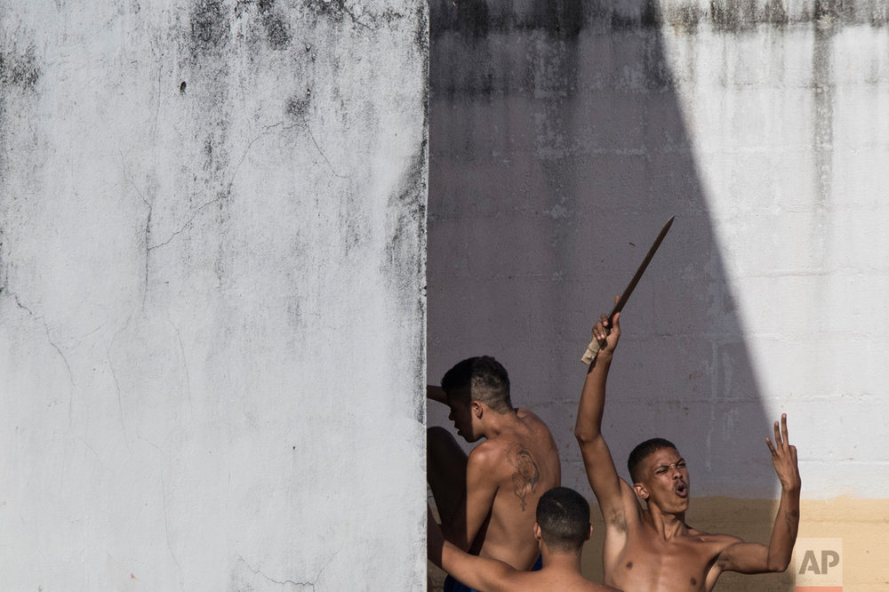An inmate holds up a makeshift knife moments after police left the prison in the Alcacuz prison in Nisia Floresta, near Natal, Brazil, on Tuesday, Jan. 24, 2017. Military police had entered the facility in northeastern Brazil where a temporary wall separating two rival gangs is being built, after a week of chaos and fighting between rival gangs that left dozens of inmates dead. (AP Photo/Felipe Dana)