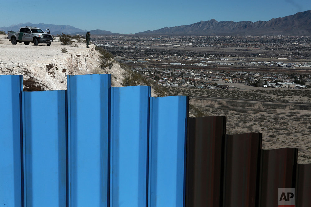 A border patrol agent, watches the Mexico-U.S. border fence, on the Mexican side, separating the towns of Anapra, Mexico and Sunland Park, N.M., on Wednesday, Jan. 25, 2017. (AP Photo/Christian Torres)