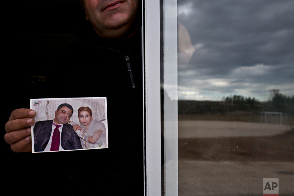 "In this Thursday, Jan. 5, 2017 photo, Henef Slu, 37, a Syrian refugee from Aleppo's northern district of Sheikh Maqsud, holds a photograph of his wedding day, from the window of his shelter in Ritsona refugee camp, Greece. ""It was the most beautiful day of my life the day I married my wife Nadima, we had a lot of guests, family and friends, this photograph was the only thing we carried with us from home."" Henef said. (AP Photo/Muhammed Muheisen)"