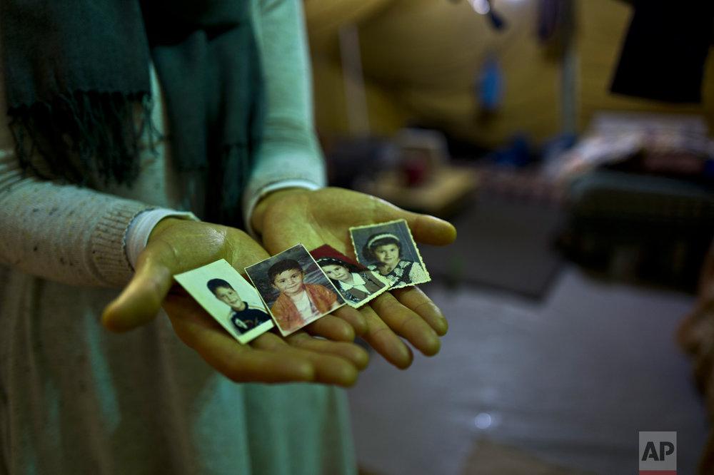 "In this Tuesday, Jan. 17, 2017 photo, Sahar Dargzini, 40, a Syrian refugee from Baghdad street in Damascus, shows photographs of her children when they were young, from right, Amal who currently is 24 and lives in Norway, Dania who currently is 26 and lives in Turkey, Mohyeddin, who currently is 15 and lives in Sweden and Salahudin who currently is 20 and lives in Sweden, at her tent in Kalochori refugee camp on the outskirts of the northern Greek city of Thessaloniki. ""I love keeping my children pictures with me all the times, they will always remain my children, I hope they will allow me to go to Norway and be with my daughter and see my granddaughter Mirna."" Sahar said. (AP Photo/Muhammed Muheisen)"