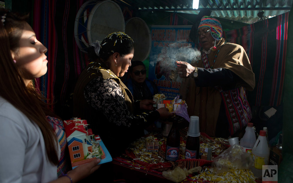 In this Jan. 24, 2017 photo, an Aymara indigenous spiritual guide blesses statues of a miniature home and miniature food for a client during the Alasitas Fair in downtown La Paz, Bolivia. During the pre-Columbian festival, Bolivians buy tiny replicas of things they aspire to as they strive to improve their lives in South America's poorest nation. (AP Photo/Juan Karita)