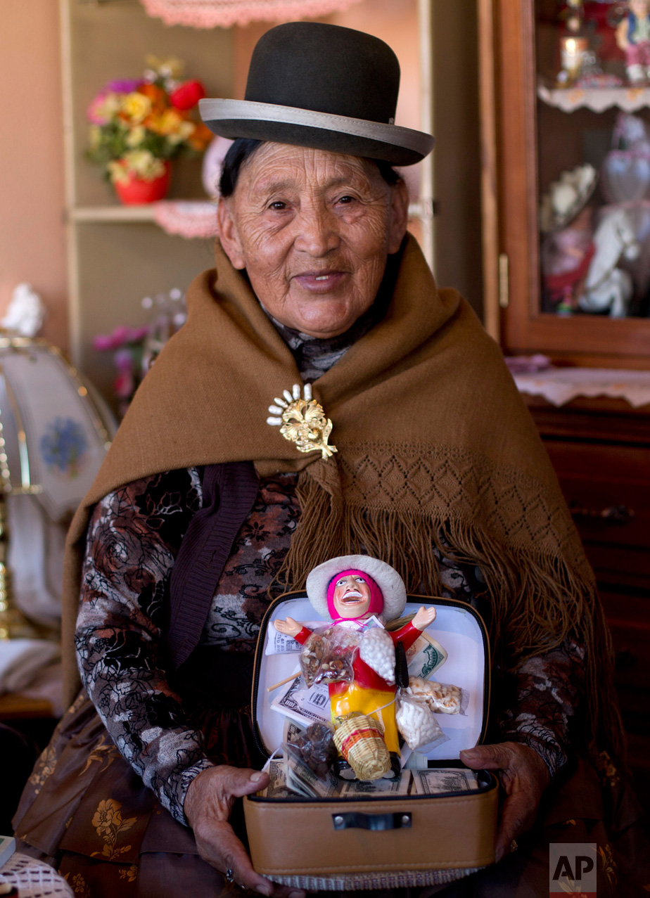 "In this Jan. 29, 2017 photo, Hilda Rosa Medina poses for a portrait with her Ekeko and fake currency inside her home during the annual Alasita fair in La Paz, Bolivia. Medina, age 72, said ""Every Jan. 24 it's a family tradition, since the time of my grandparents, to buy at the Alesita with a lot of faith, and it comes true."" During the pre-Columbian tradition people buy tiny replicas of things they aspire to. (AP Photo/Juan Karita)"
