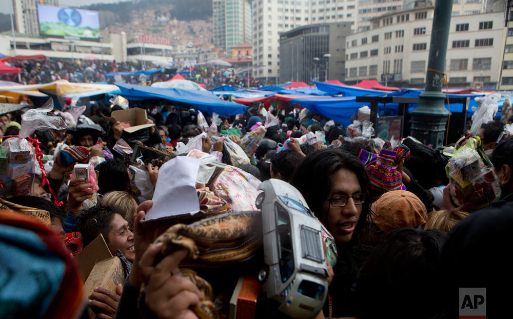 In this Jan. 24, 2017 photo, people attend the annual Alasitas fair, some holding their miniature items, in downtown La Paz, Bolivia. Thousands of working class-Bolivians crowd the streets of La Paz every year to buy miniature cars, houses and wads of fake dollar bills representing their dreams of wealth. (AP Photo/Juan Karita)