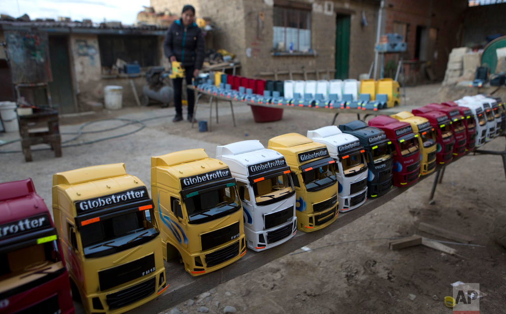 In this Jan. 16, 2017 photo, miniature trucks dry from a fresh paint job at a workshop in El Alto, Bolivia, ahead of the annual Alesitas Fair. Tiny replicas of items people dream of acquiring are taken home and placed around a statue of Ekeko, the Aymara god of abundance, who the Aymara people believe will bless them with better lives in the coming year. (AP Photo/Juan Karita)
