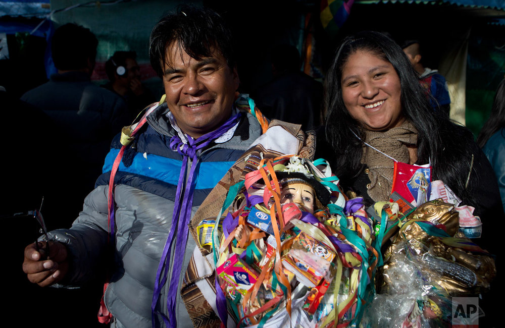 "In this Jan. 24, 2017 photo, husband and wife, Bautista Acuna and Ana Mayta, hold an Ekeko, the Aymara god of abundance, as they pose for a portrait at the annual Alasita Fair in downtown La Paz, Bolivia. ""I faithfully believe in Ekeko. Thanks to him, I have everything I've asked for,"" said Acuna, a 44-year-old car-importer. ""I asked for money, and I got it,"" he said. ""I asked for a house, and I got it; I asked for a business, and I got it."" (AP Photo/Juan Karita)"