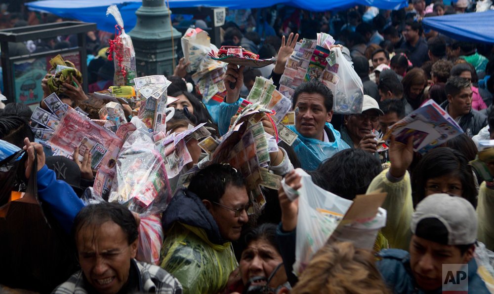 In this Jan. 24, 2017 photo, people raise miniature items to be blessed by altar servers with holy water outside San Francisco Basilica during the annual Alasitas Fair in downtown La Paz, Bolivia. Thousands of working class-Bolivians crowd the streets of La Paz every year to buy miniature cars, houses and wads of fake dollar bills representing their dreams of wealth. (AP Photo/Juan Karita)