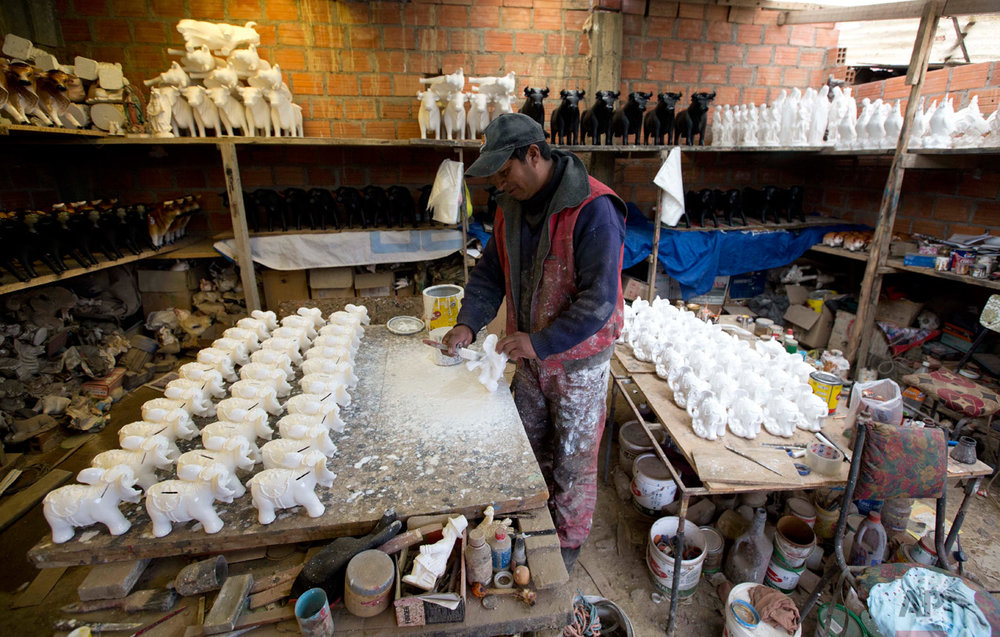 "In this Jan. 13, 2017 photo, an artisan paints coin savers shaped as elephants at a workshop in El Alto, Bolivia, to sell at the Alesia Fair. The Aymara word ""alasita"" means ""buy me."" (AP Photo/Juan Karita)"