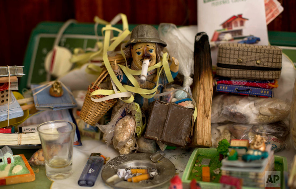 In this Jan. 27, 2017 photo, an Ekeko dressed as a miner holds a partially smoked cigarette in its mouth, surrounded by miniature objects inside the home of Ana Rosario Azuga, during the annual Alasita Fair in La Paz, Bolivia. The Ekeko is the fair's central character, revered as the Aymara god of abundance. (AP Photo/Juan Karita)