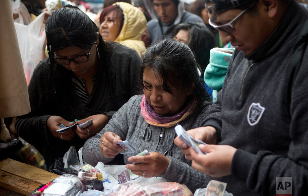 In this Jan. 24, 2017 photo, a woman counts her fake money after buying it at the annual Alasitas Fair in downtown La Paz, Bolivia. Thousands of working class-Bolivians crowd the streets of La Paz every year to buy miniature cars, houses and wads of fake dollar bills representing their dreams of wealth. (AP Photo/Juan Karita)