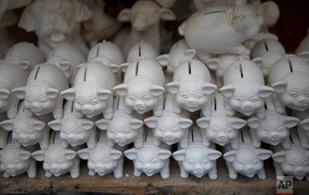 In this Jan. 13, 2017 photo, clay piggy banks are stacked before getting a paint job at a workshop in El Alto, Bolivia. Artisans create miniatures for the annual Alasitas Fair, a pre-Columbian tradition where people buy tiny replicas of things they dream of owning. (AP Photo/Juan Karita)