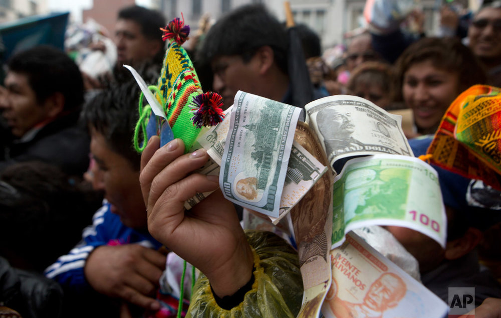 In this Jan. 24, 2017 photo, a man holds up fake currency to be blessed by altar servers outside of the Basilica of San Francisco during the annual Alasitas fair in downtown La Paz, Bolivia. Thousands of working class-Bolivians crowd the streets of La Paz every year to buy miniature cars, houses and wads of fake dollar bills representing their dreams of wealth. (AP Photo/Juan Karita)