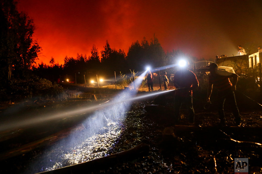 In this Sunday, Jan. 29, 2017 photo, a resident wets down the ground surrounding his home, threatened by a nearby wildfire in Portezuelo, Chile. Residents of some communities have been battling the fires themselves, without any protective gear and often using just branches or bottles of water in a frantic effort to save their homes, pasture and livestock. But those efforts are often undone as winds or smoldering ash spread the fires anew. (AP Photo/Esteban Felix)