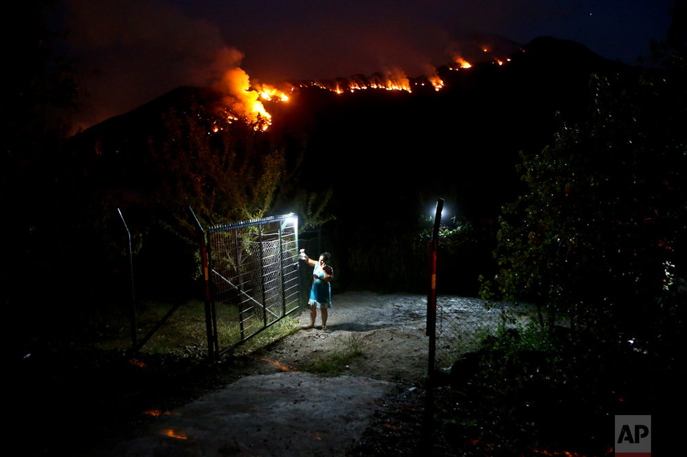In this Tuesday, Jan. 24, 2017 photo, a woman closes a gate on her land as wildfires rage on a nearby mountain in Cajon del Maipo, on the outskirts of Santiago, Chile. Chile is suffering one of its worst fire disasters in history. The fires have outpaced local ability to put them out, forcing Chile to request international aid. (AP Photo/Esteban Felix)