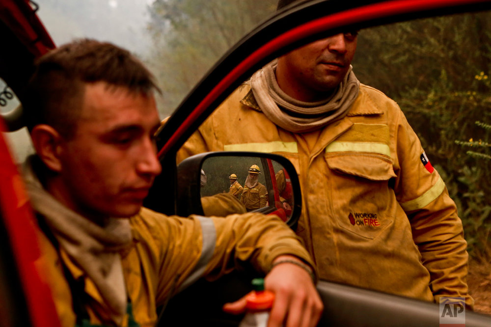 In this Friday, Jan. 27, 2017 photo, firefighters takes a break from digging trenches, as wildfires threaten Florida, a community of Concepcion, Chile. More than 20,000 people, including firefighters and experts from more than a dozen countries, have battled wildfires that President Michelle Bachelet has called the worst forest disaster in Chile's history. (AP Photo/Esteban Felix)