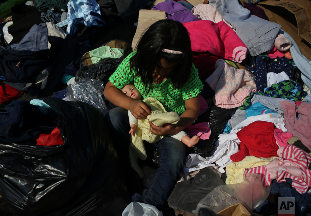 Jenny Tapia dresses her doll with clothes donated to victims of Chile's raging wildfires, in the community of Santa Olga, Chile, Tuesday, Jan. 31, 2017. Flames from one of the country's worst wildfires completely consumed the town of Santa Olga. (AP Photo/Esteban Felix)