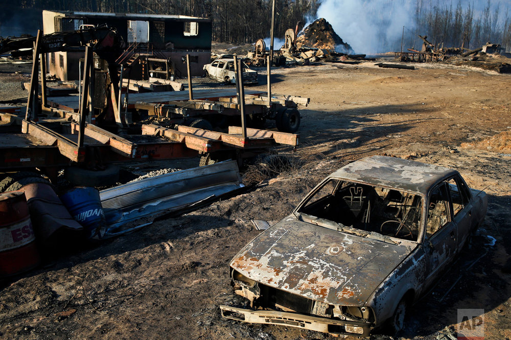 Scorched trees, vehicles and debris cover the landscape of a sawmill consumed by wildfires in the community Santa Olga, Chile, Tuesday, Jan. 31, 2017. The fires have been raging in central and southern Chile, fanned by strong winds, hot temperatures and a prolonged drought. (AP Photo/Esteban Felix)