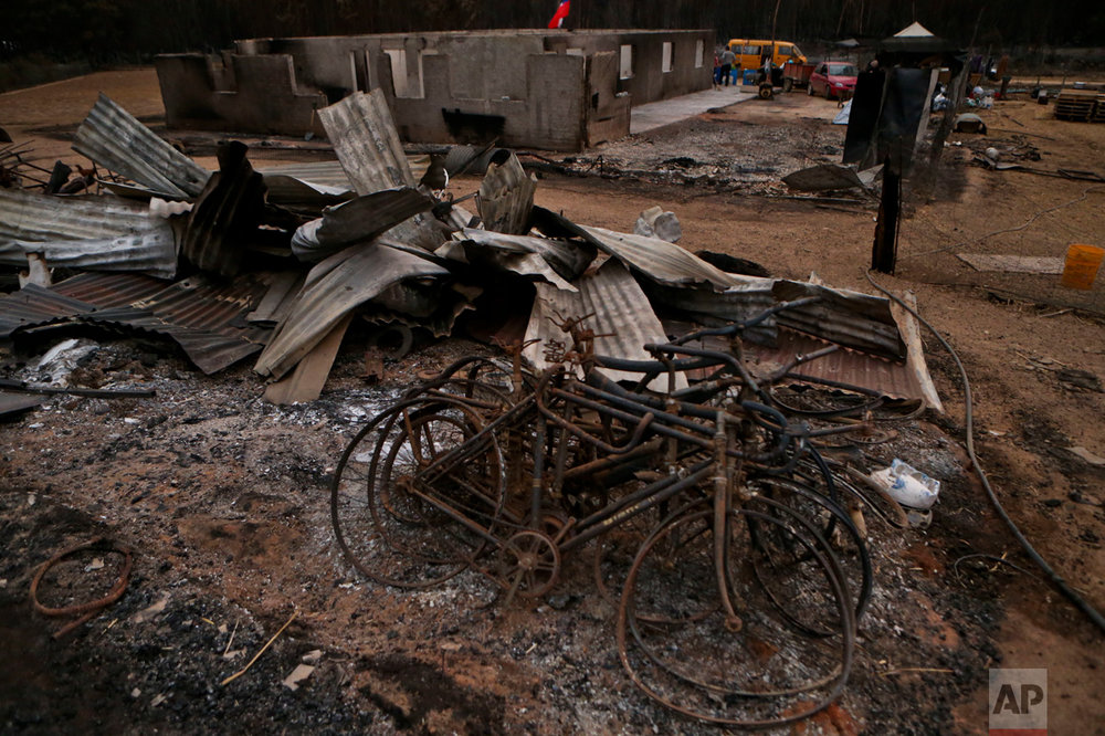 This Saturday, Jan. 21, 2016 photo shows charred bicycles amid debris left from wildfires in Pumanque, Chile. The fires have consumed forests, livestock and entire towns, prompting President Michelle Bachelet to declare a state of emergency, deploy troops and ask for international help. (AP Photo/Esteban Felix)