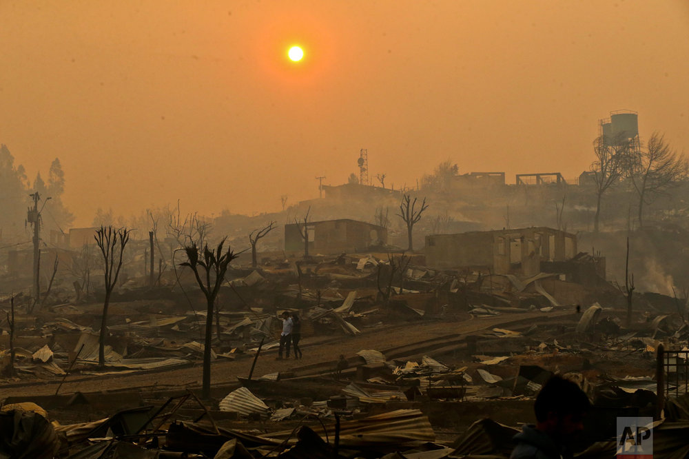 In this Thursday, Jan. 26, 2017 photo, a couple walks through a neighborhood destroyed by wildfires in Chile's Santa Olga community. Officials say the town was consumed by the country's worst wildfires, engulfing the post office, a kindergarten and hundreds of homes. (AP Photo/Esteban Felix)