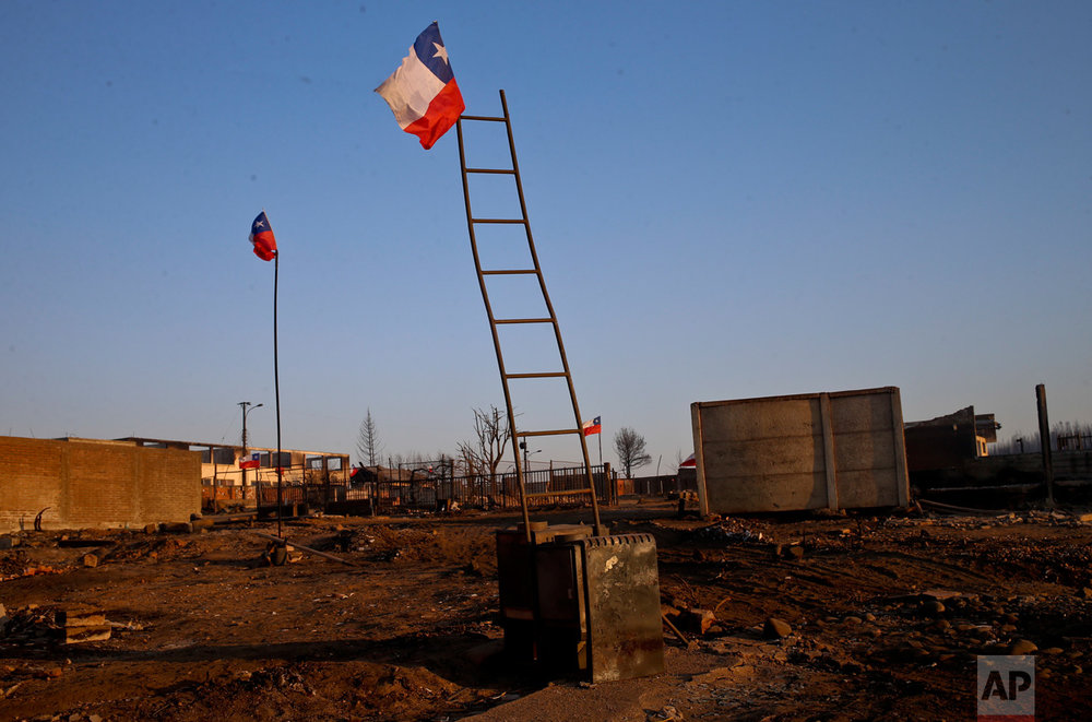 National flags fly over the scorched landscape of Chile's Santa Olga community, Tuesday, Jan. 31, 2017. The national forestry agency says Chile's raging wildfires have destroyed nearly 904,000 acres (366,000 hectares) since Jan. 15. (AP Photo/Esteban Felix)