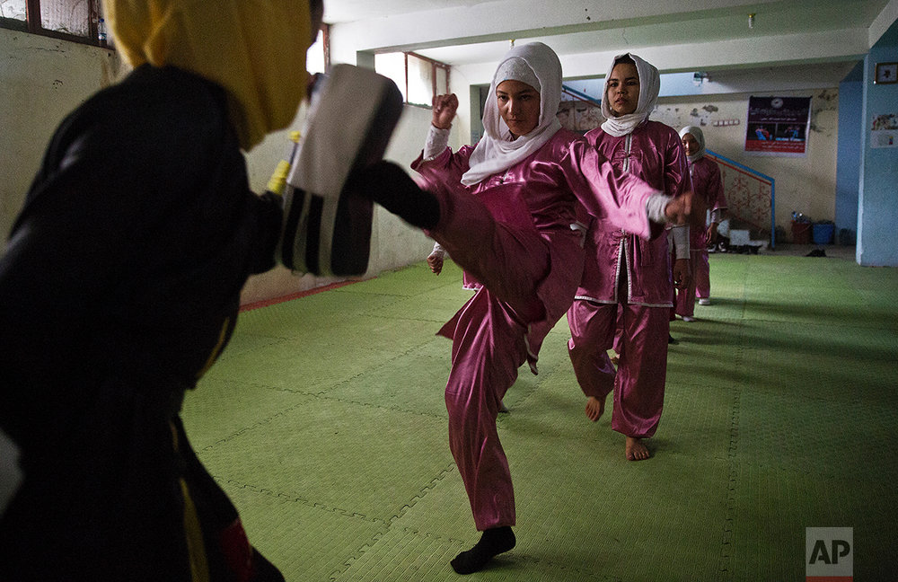 Shaolin martial arts students practice at their club in Kabul, Afghanistan, Tuesday, Jan. 25, 2017. When they aren't training on the snow covered hills that surround Kabul, Azimi, teacher wearing black, trains her students in a grungy, dark club financed by a young cinema actor. (AP Photos/Massoud Hossaini)