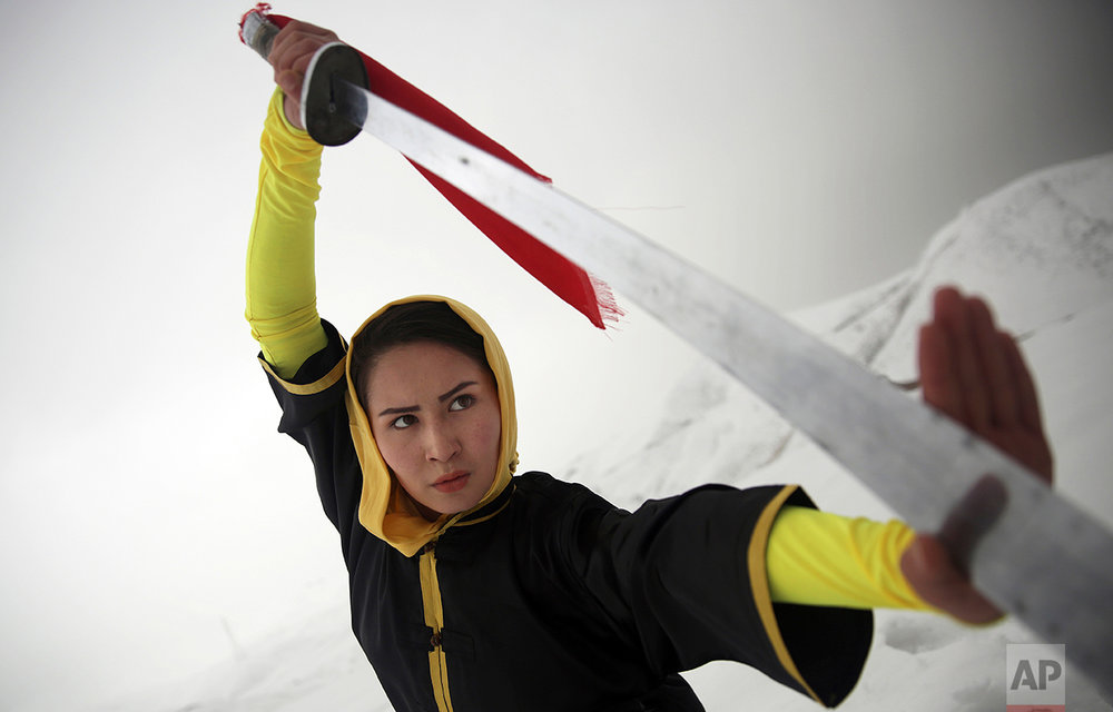 Shaolin martial arts trainer, Sima Azimi, 20, performs on a hilltop in Kabul, Afghanistan, Tuesday, Jan. 25, 2017. Azimi said it was difficult to find all the tools needed to train. For instance, she had to order her Shaolin sword from Iran, where she had studied the art for three years. (AP Photos/Massoud Hossaini)