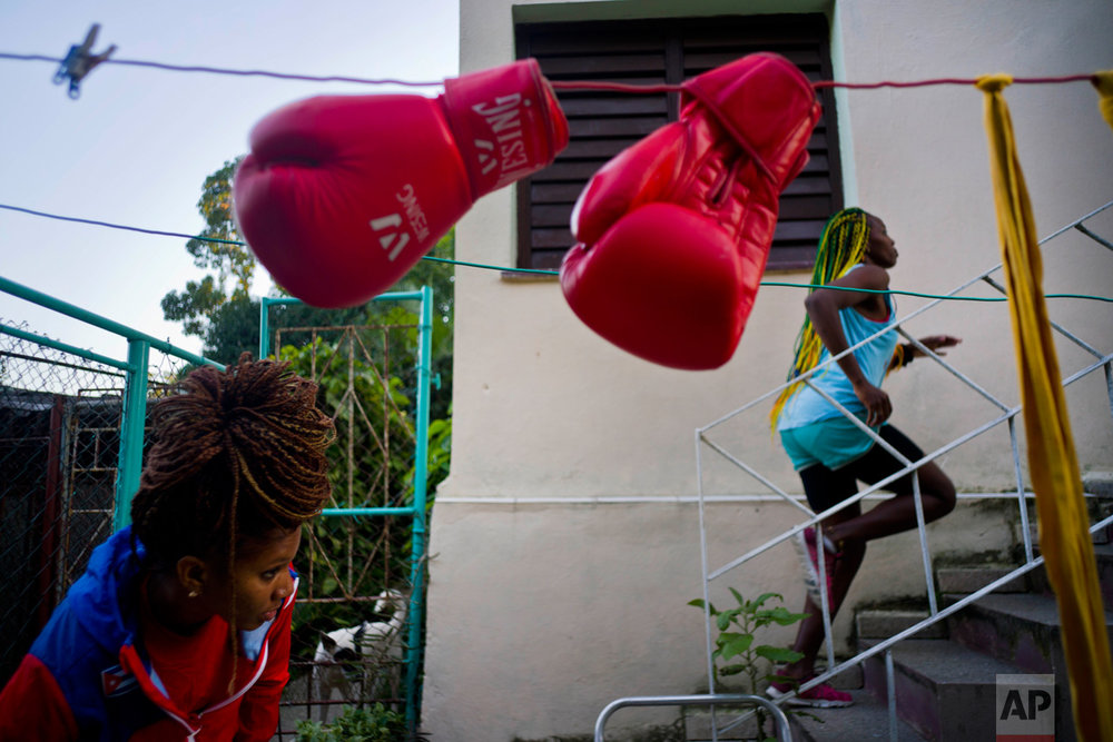 "In this Jan. 19, 2017 photo, boxer Legnis Cala runs up a flight of stairs in the backyard of her house, in Havana, Cuba. ""I see myself at the Olympics in Japan 2020,"" Moreno said. ""That's my dream."" Pictured at bottom left is boxer Idamelys Moreno. (AP Photo/Ramon Espinosa)"